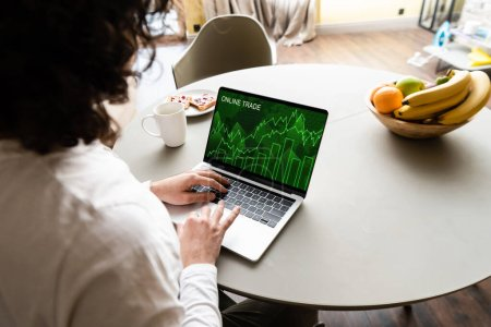 Photo pour Vue arrière de pigiste à l'aide d'un ordinateur portable avec site de commerce en ligne près de fruits, tasse de café et assiette avec des toasts - image libre de droit