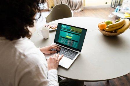 vue arrière de pigiste à l'aide d'un ordinateur portable avec site Sportsbet près de fruits, tasse de café et assiette avec des toasts