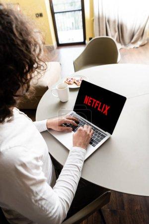 Photo pour KYIV, UKRAINE - 25 AVRIL 2020 : vue en grand angle du pigiste à l'aide d'un ordinateur portable avec Netflix à l'écran près d'une tasse de café et plaque avec des toasts - image libre de droit