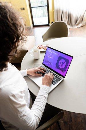 vue grand angle de pigiste à l'aide d'un ordinateur portable avec site web de shopping près de tasse de café et plaque avec des toasts