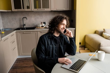 Photo for Smiling freelancer talking on smartphone near laptop and coffee cup in kitchen - Royalty Free Image