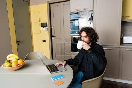 Photo pour KYIV, UKRAINE - 25 AVRIL 2020 : beau café freelance tout en utilisant un ordinateur portable près du smartphone avec application Skype, carte de crédit et fruits frais - image libre de droit