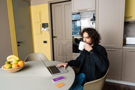 Photo pour KYIV, UKRAINE - 25 AVRIL 2020 : beau freelance buvant du café tout en utilisant un ordinateur portable près du smartphone avec application Instagram, carte de crédit et fruits frais - image libre de droit