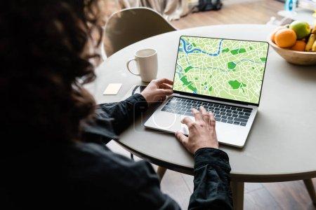 Photo pour Vue arrière de pigiste à l'aide d'un ordinateur portable avec carte à l'écran près de tasse de café, notes collantes et fruits - image libre de droit