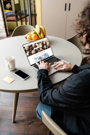 Photo for KYIV, UKRAINE - APRIL 25, 2020: back view of freelancer using laptop with Depositphotos website near smartphone, coffee cup and fresh fruits - Royalty Free Image