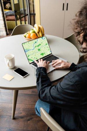 vista posterior del freelancer utilizando el ordenador portátil con mapa en la pantalla cerca de teléfono inteligente, taza de café, notas adhesivas y frutas