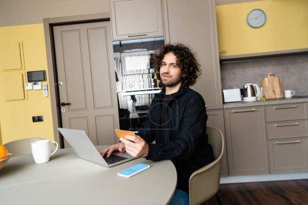 Photo pour KYIV, UKRAINE - 25 AVRIL 2020 : beau freelance souriant à la caméra tout en tenant la carte de crédit et en utilisant un ordinateur portable près du smartphone avec l'application Skype à l'écran - image libre de droit