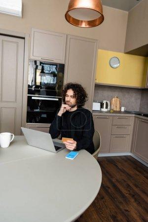 Photo pour KYIV, UKRAINE - 25 AVRIL 2020 : une pigiste réfléchie tenant une carte de crédit tout en regardant un ordinateur portable près d'un smartphone avec l'application Skype à l'écran - image libre de droit