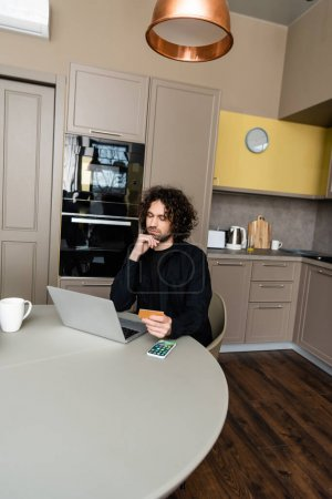 Photo for KYIV, UKRAINE - APRIL 25, 2020: thoughtful freelancer holding credit card while looking at laptop near Apple smarphone with homepage on screen - Royalty Free Image