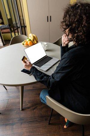 Rückansicht des Freiberuflers mit Kreditkarte am Laptop sitzend mit weißem Bildschirm, Smartphone und Obst