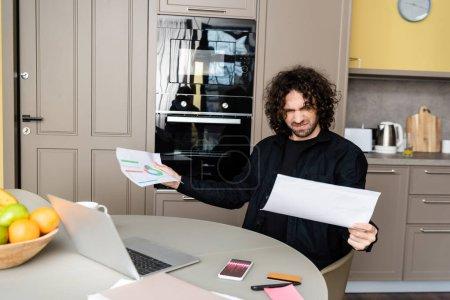 Photo pour Concentration sélective des papiers de tenue freelance confus avec des graphiques près de l'ordinateur portable et smartphone avec des graphiques à l'écran dans la cuisine - image libre de droit
