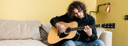Photo for Panoramic shot of handsome man playing acoustic guitar on couch - Royalty Free Image