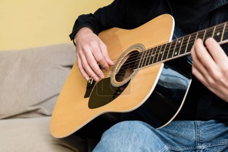 Photo for Cropped view of man playing acoustic guitar on sofa at home - Royalty Free Image
