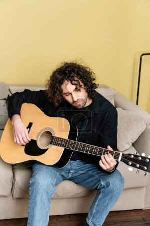 Photo for Handsome curly man playing acoustic guitar on couch in living room - Royalty Free Image