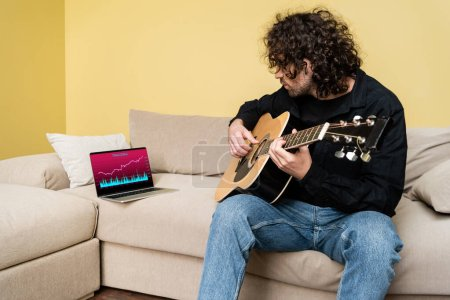 Photo for Curly man playing acoustic guitar near laptop with trading website on couch - Royalty Free Image