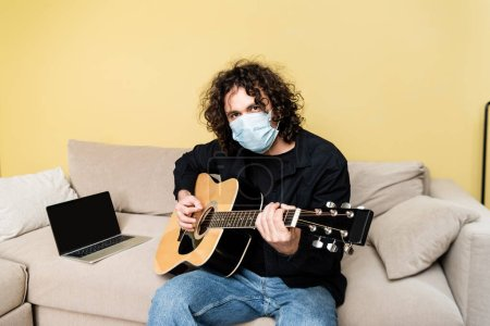 Photo for Man in medical mask playing acoustic guitar near laptop on sofa - Royalty Free Image