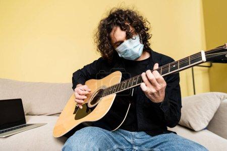 Photo pour Homme en masque médical jouant de la guitare acoustique près d'un ordinateur portable sur un canapé à la maison - image libre de droit