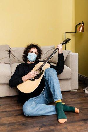 Photo pour Homme en masque médical regardant la caméra tout en jouant de la guitare acoustique sur le sol près du canapé - image libre de droit