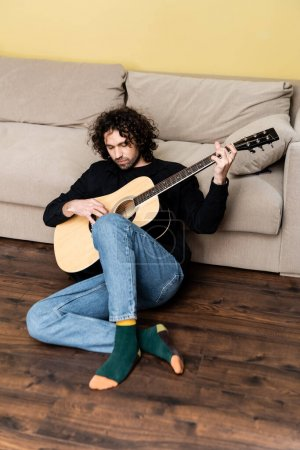 Photo for Handsome man performing on acoustic guitar on floor in living room - Royalty Free Image