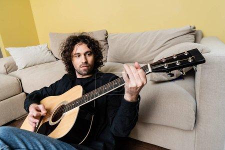 Photo pour Focus sélectif du bel homme jouant de la guitare acoustique assis sur le sol à la maison - image libre de droit