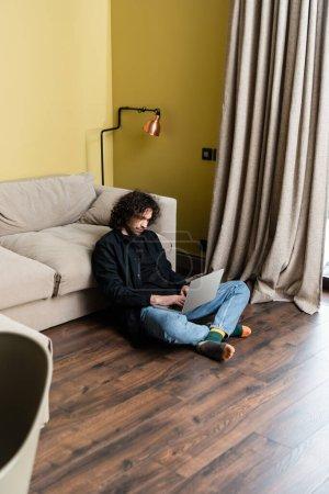 Photo pour Selective focus of beautiful man using laptop on floor at home - image libre de droit