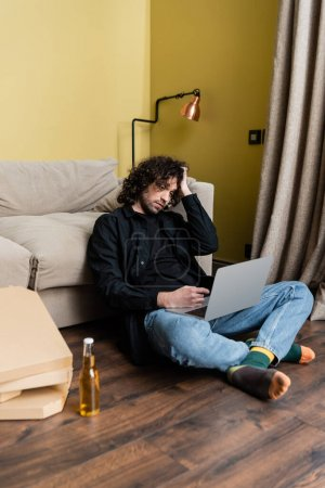 Photo for Selective focus of teleworker pointing with finger at laptop near beer and pizza boxes on floor - Royalty Free Image