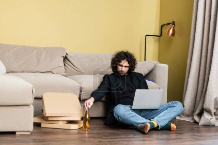 Freelancer holding bottle of beer near laptop and pizza boxes on floor in living room