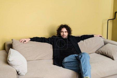 Photo pour Beau homme assis sur le canapé dans le salon - image libre de droit