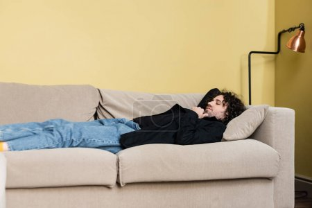 Photo for Side view of man lying on couch in living room - Royalty Free Image