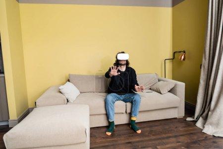 Photo pour Homme bouclé jouant à un jeu vidéo en réalité virtuelle casque sur canapé - image libre de droit