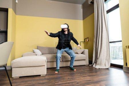 Photo pour Homme jouant à un jeu vidéo en réalité virtuelle casque à la maison - image libre de droit