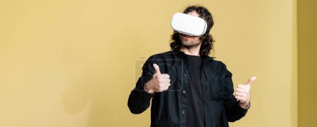 Photo for Panoramic shot of man in vr headset showing like gesture at home - Royalty Free Image