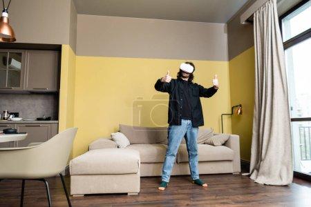 Foto de Hombre mostrando como gesto mientras utiliza auriculares de realidad virtual en el salón. - Imagen libre de derechos