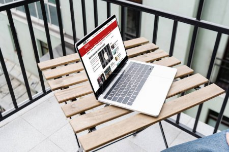 Photo pour KYIV, UKRAINE - 25 AVRIL 2020 : Vue recadrée de l'homme assis près d'un ordinateur portable avec le site de nouvelles de la bbc sur le balcon - image libre de droit