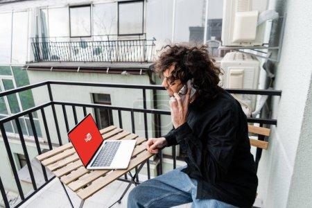 KIEW, UKRAINE - 25. APRIL 2020: Freelancer im Gespräch auf dem Smartphone in Laptopnähe mit Youtube-Website auf dem Tisch auf dem Balkon
