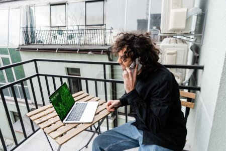 Photo for Man talking on smartphone near laptop with online trade website on balcony - Royalty Free Image