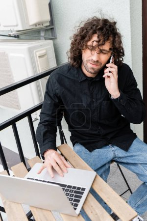 Selective focus of handsome man talking on smartphone and using laptop on balcony at home