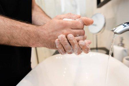 Photo pour Vue recadrée de l'homme se lavant les mains avec du savon dans la salle de bain - image libre de droit