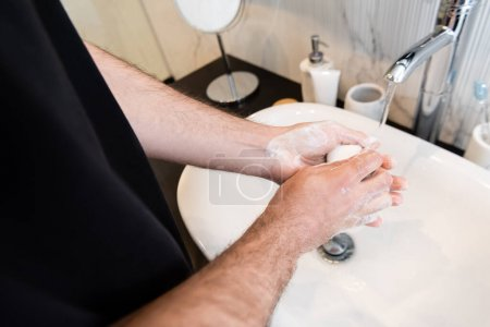 Photo for Cropped view of man holding soap while washing hands in bathroom - Royalty Free Image