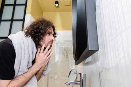 Photo pour Vue latérale de beau bouclé homme toucher le visage tout en regardant miroir dans la salle de bain - image libre de droit