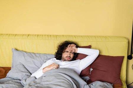 Photo pour Homme bouleversé avec la main près du front couché sur le lit à la maison - image libre de droit
