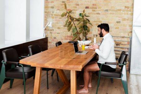 Photo pour Homme afro-américain barbu en chemise et sous-vêtements assis près d'un ordinateur portable et gestuelle tout en ayant appel vidéo - image libre de droit