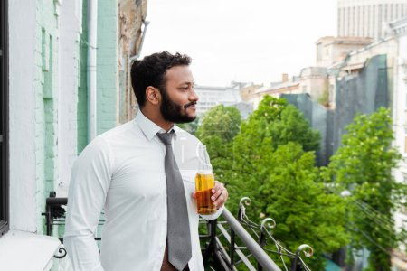 Photo for Side view of happy african american man holding bottle of beer on balcony - Royalty Free Image