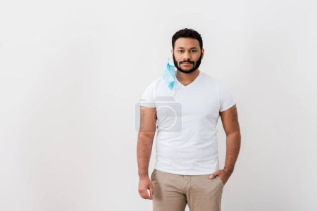 bearded african american man in blue medical mask standing with hand in pocket near white wall