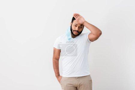 Foto de Hombre afroamericano enfermo en máscara médica de pie con la mano en el bolsillo y tocando la frente cerca de la pared blanca - Imagen libre de derechos