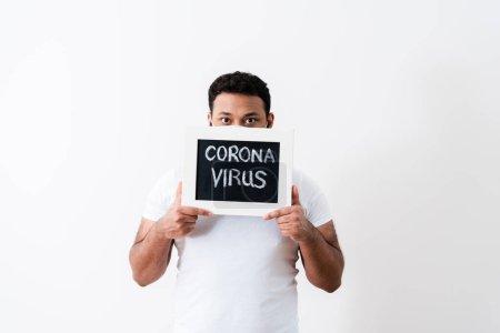 Afrikanisch-amerikanischer Mann in medizinischer Maske bedeckt Gesicht mit Coronavirus-Schriftzug auf Kreidetafel nahe weißer Wand