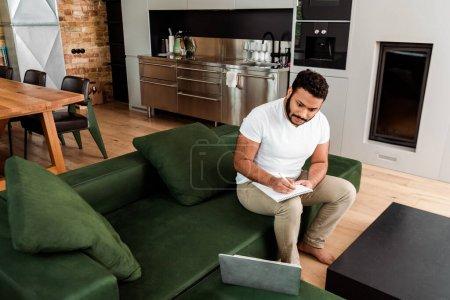 Photo pour Bel homme afro-américain écrit dans un cahier près d'un ordinateur portable, étude concept en ligne - image libre de droit