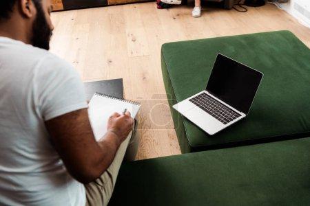 Photo pour Foyer sélectif de barbu homme afro-américain écrit dans un ordinateur portable près de l'ordinateur portable avec écran blanc, étude concept en ligne - image libre de droit