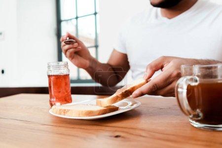 Photo pour Vue recadrée de l'homme afro-américain tenant cuillère près du bocal avec confiture sucrée et pain grillé sur assiette - image libre de droit