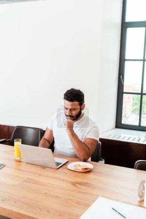 Photo pour Cher freelance afro-américain regardant ordinateur portable près du petit déjeuner sur la table - image libre de droit